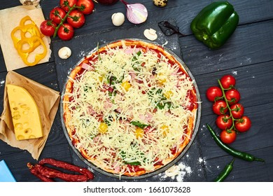 Raw pizza with mozzarella cheese, meat, tomatoes, mushrooms, peppers, herbs on a dark wooden background. Cooking delicious italian pizza.