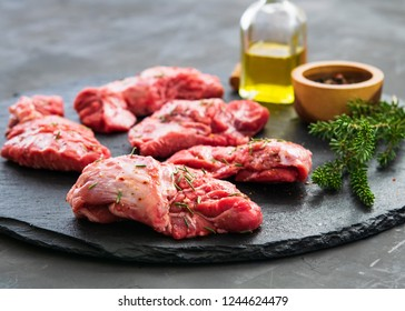 Raw pork cheeks meat on a dark gray surface with rosemary and spices. Food background with copy space. Horizontal. Space for text.