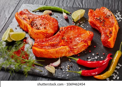 raw pork chops prepared to cook, marinated with spices and red sriracha sauce on black slate tray with chili pepper, salt, lime slices and spices, view from above, close-up