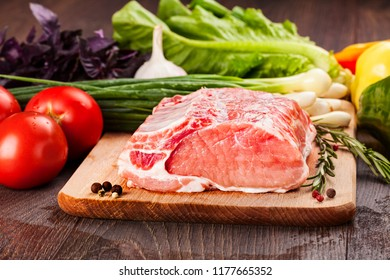 Raw pork for cooking and  barbecue on cutting board with vegetables.