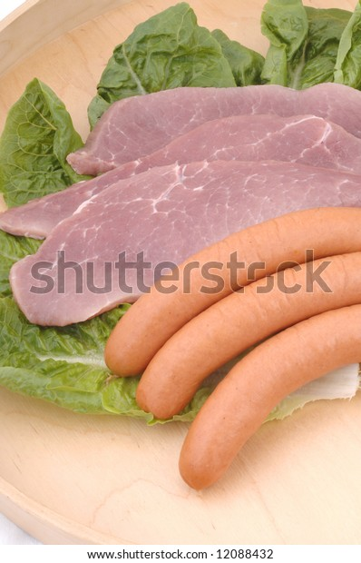Raw pork meat and sausage over green salad