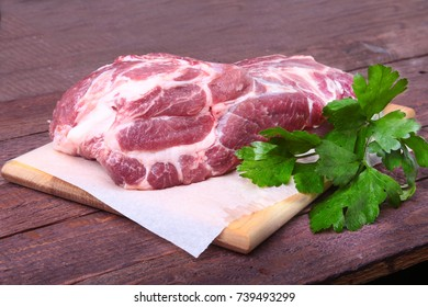 Raw pork neck chop meat with parsley herb leaves on a stone background. Ready for cooking.