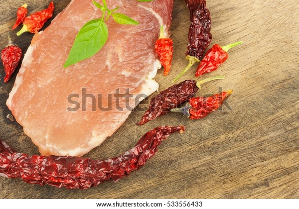 Raw pork on a wooden background. Dried chillies. Preparing spicy food. Spices for cooking meat.