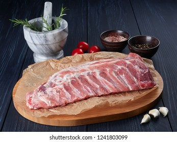 Raw pork ribs on crumpled paper on a bamboo cutting board, with rosemary twigs, tomatoes, garlic cloves, peppercorns and coarse pink salt