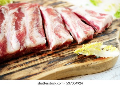 raw pork ribs on a cutting board, closeup