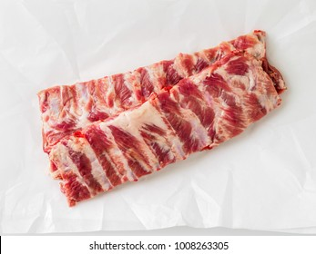 raw pork ribs on white parchment paper, top view