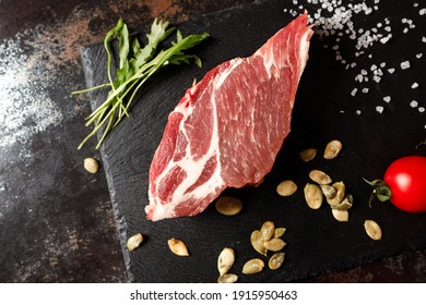 raw pork with spices for cooking on a fire or oven on a dark stone background