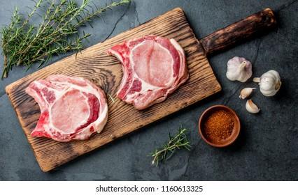 Raw pork steaks with seasoning on wooden board. Gray slate background.