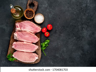 raw pork steaks with spices on a cutting board on a stone background with copy space for your text