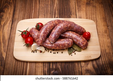 Raw pork thick sausages on cutting board with spices
