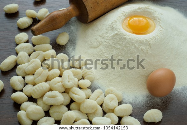 Raw potato gnocchi with eggs, flour and rolling pin on a wooden table