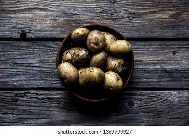 Raw potatoes in bowl on wooden table. Close up view