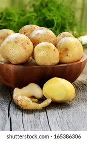 Raw potatoes in bowl on wooden table