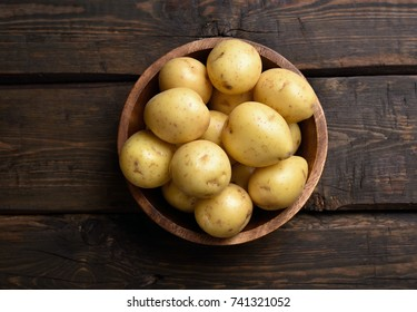 Raw potatoes in bowl on wooden table with copy space, top view.