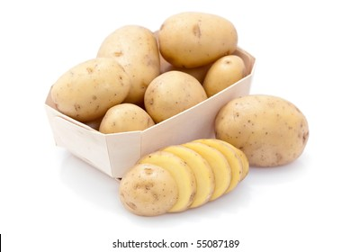 Raw potatoes in carton with sliced one in foreground, isolated on white.