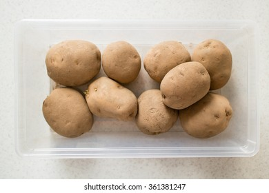 Raw potatoes in a plastic container.