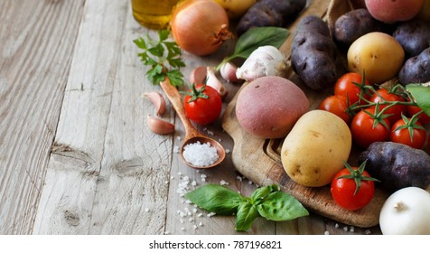Raw potatoes and vegetables on a wooden board