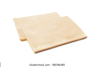 Raw puff pastry on white background