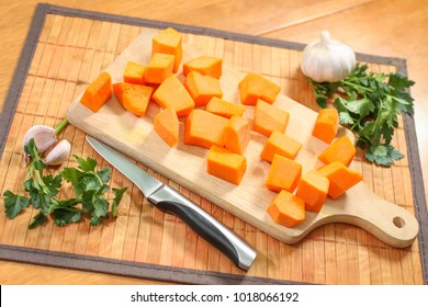 Raw pumpkin chopped on the cutting board, prepared for making pumpkin soup.