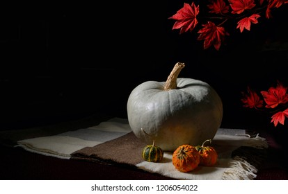raw pumpkin on rustic carpet on black background