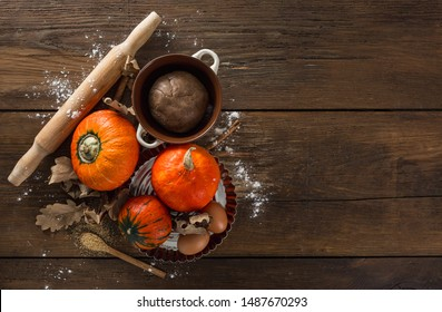 Raw pumpkin pie dough with dry autumn leaves, cane sugar, rolling pin and cinnamon sticks on wooden background with copy space