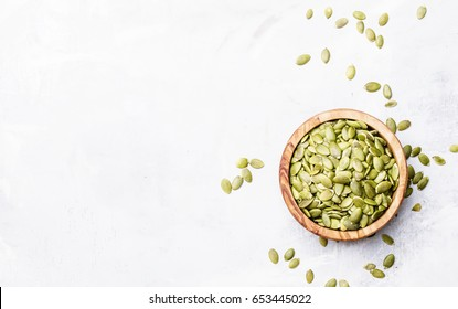 Raw pumpkin seeds, food background, top view - Shutterstock ID 653445022