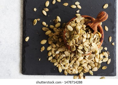 Raw pumpkin seeds on black slate background top view