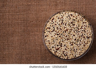 Raw Quinoa seeds in glass bowl on darck background top view, space for text. Vegan protein source. Superfoods and Healthy food clean eating.