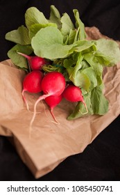 Raw radishes with leaves on paper bag and black background.