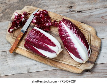 Raw red chicory on a wooden board close up