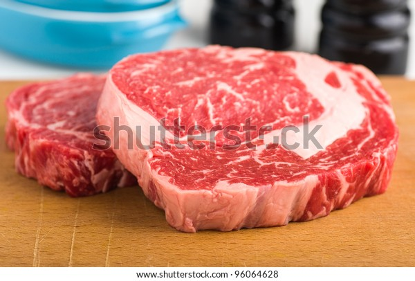 Raw red meat beef ribeye steak on wood plank