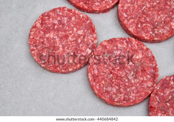Raw red meat burgers for hamburgers of minced ground beef or pork on white parchment paper ready for cooking