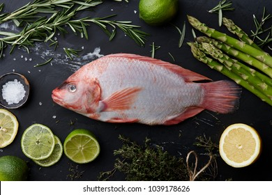 Raw red tilapia fish cooking with herbs, spices, green asparagus, lemon and lime on black stone background, top view