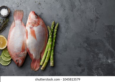 Raw red tilapia fish cooking with herbs, spices, green asparagus, lemon and lime on gray stone background, top view