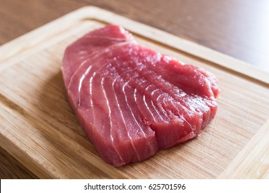 Raw red tuna steak on wooden chopping board. Tonno rosso used for tartarre or sushi