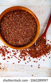 Raw red wild rice in a bowl and spoon on a wooden background. Ingredient for a healthy diet.