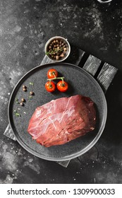 Raw reindeer meat on a black plate on a dark background