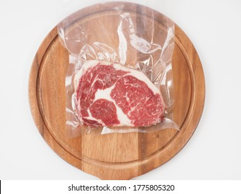 raw rib beef steak in vacuum seal plastic bag on white background.