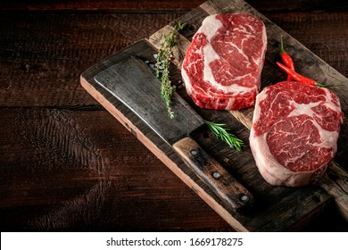 Raw rib eye steak of beef on a wooden Board with a meat cleaver and seasonings