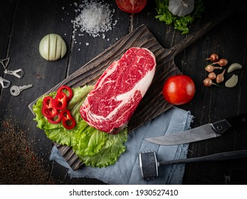 Raw ribeye beef steak with ingredients on a wooden cutting board . Top view.
