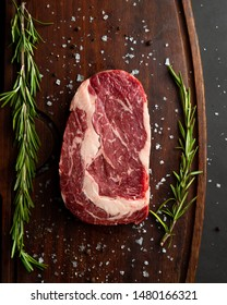 Raw ribeye steak with fresh rosemary on wooden cutting board, top down view. Vertical orientation