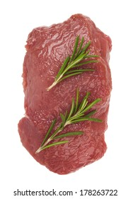 Raw ribeye steak garnished with a sprig of rosemary.
