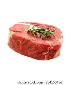 Raw ribeye steak garnished with sprig of rosemary, isolated