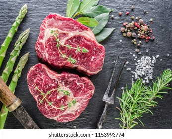 Raw Ribeye steaks or beef steak on graphite tray with herbs. Top view.