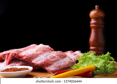Raw Ribs on a rustic cutting board with salt, pepper and grinder for spices . Black Background for copy space. Top View.
