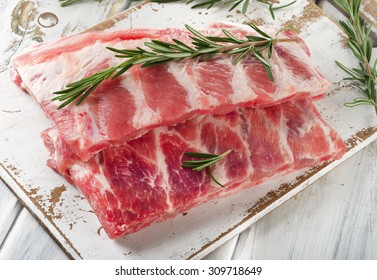 Raw ribs with a rosemary on a white wooden table