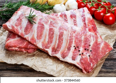 Raw ribs with a rosemary and vegetables. on crumpled paper