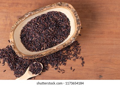 Raw rice berry with wooden bowl and spoon with selective focus, Flat lay