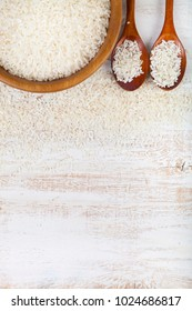 Raw rice in a bowl on a wooden background. Ingredient for a healthy diet.