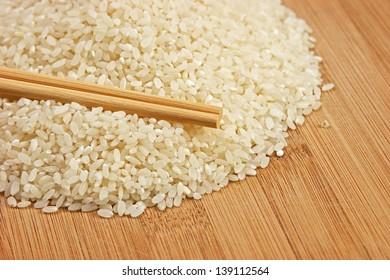 raw rice and chopsticks on bamboo board